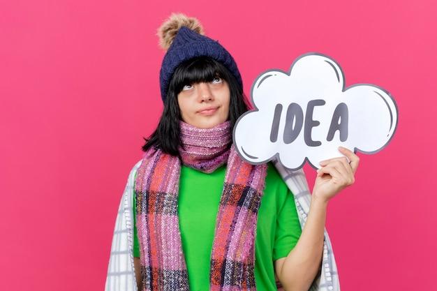 겨울 모자와 스카프를 착용하는 젊은 아픈 백인 여자 복사 공간이 진홍색 배경에 고립 찾고 생각 거품을 들고 격자 무늬에 싸여