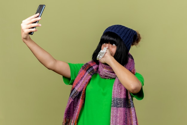Young ill caucasian girl wearing winter hat and scarf taking selfie holding napkin keeping hand on mouth isolated on olive green background with copy space