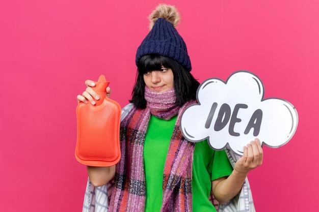 Giovane ragazza caucasica malata che indossa il cappello e la sciarpa di inverno avvolti in plaid che tiene la bolla di idea e la borsa dell'acqua calda che esamina la borsa dell'acqua calda isolata su fondo cremisi con lo spazio della copia