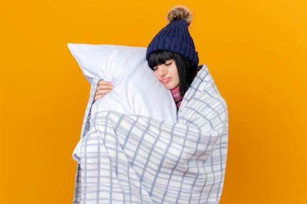 Giovane ragazza caucasica malata che indossa un cappello e una sciarpa invernali avvolti in plaid che tiene il cuscino che tocca il fronte con gli occhi chiusi isolati su fondo arancio con lo spazio della copia