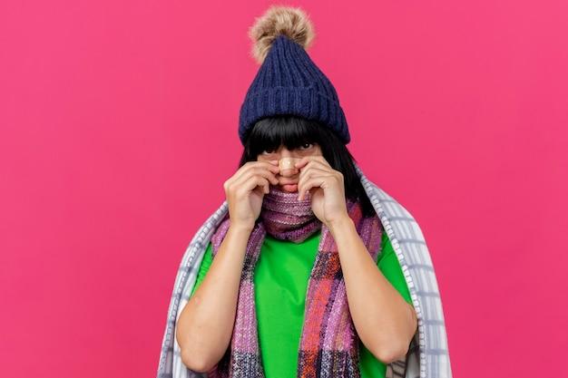 Giovane ragazza caucasica malata che indossa il cappello e la sciarpa di inverno avvolti in plaid che mette intonaco medico sul naso isolato sulla parete cremisi con lo spazio della copia