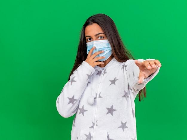 녹색 배경에 고립 된 카메라에 손을 잡고 의료 마스크를 쓰고 카메라를보고 어린 아픈 소녀