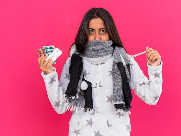 Giovane ragazza malata che guarda l'obbiettivo che indossa e bocca coperta con sciarpa tenendo il termometro con pillole isolato su sfondo rosa