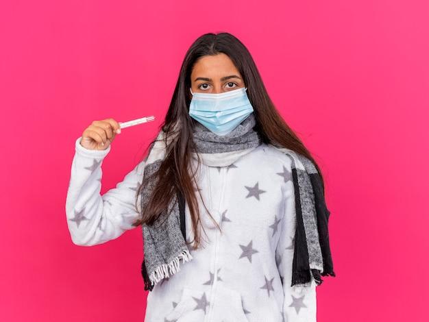 Giovane ragazza malata che guarda l'obbiettivo che indossa la mascherina medica con il termometro della tenuta della sciarpa isolato su fondo rosa