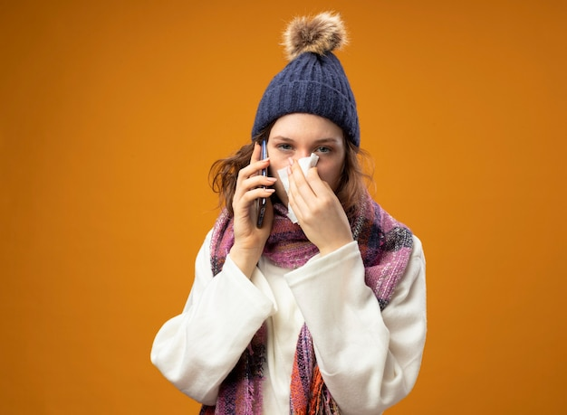 Young ill girl looking straight ahead wearing white robe and winter hat with scarf speaks on phone wiping nose with napkin isolated on orange