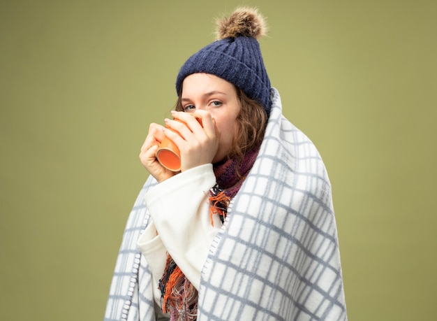Young ill girl looking straight ahead wearing white robe and winter hat with scarf wrapped in plaid drinks tea isolated on olive green
