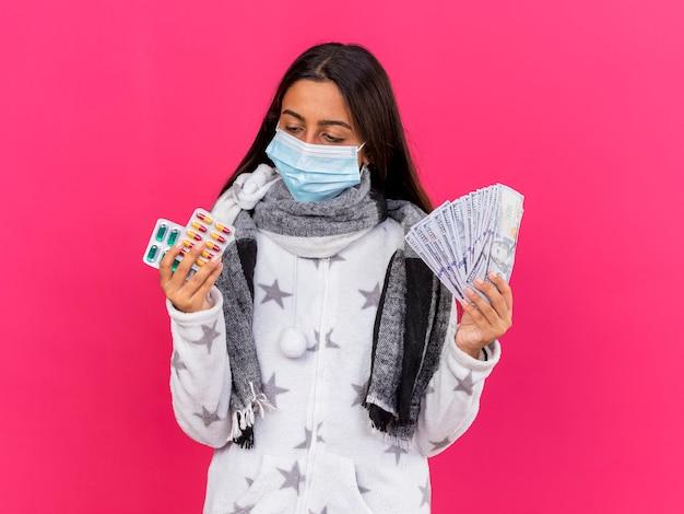 Giovane ragazza malata che indossa la mascherina medica con sciarpa tenendo i soldi e guardando le pillole in mano isolato su rosa