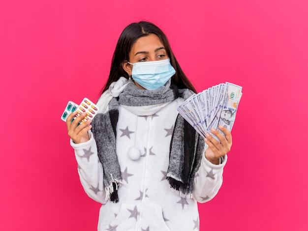 Giovane ragazza malata che indossa la maschera medica con sciarpa tenendo le pillole e guardando i contanti in mano isolato sul rosa