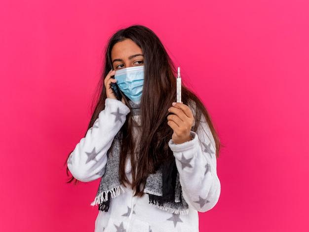 スカーフと医療マスクを身に着けている若い病気の女の子は電話で話し、ピンクで隔離された彼女の手で体温計を見て