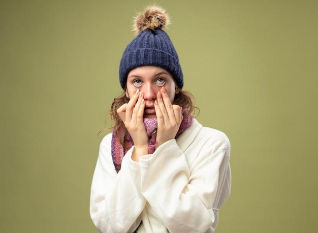 스카프가 눈 뚜껑을 아래로 당기는 흰 가운과 겨울 모자를 쓰고 아픈 소녀