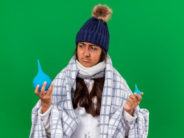 Giovane ragazza malata che indossa il cappello invernale con sciarpa tenendo e guardando i clisteri isolati su verde