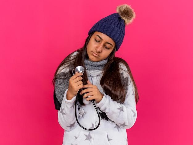 Giovane ragazza malata che indossa un cappello invernale con sciarpa tenendo e guardando lo stetoscopio isolato sul rosa