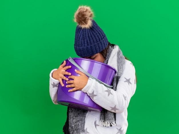 Giovane ragazza malata che indossa il cappello invernale con sciarpa che tiene secchio di plastica e vomito in esso isolato su sfondo verde