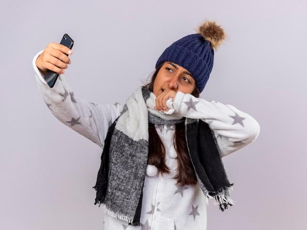 스카프와 겨울 모자를 쓰고 아픈 어린 소녀 흰색 배경에 고립 된 셀카 걸릴