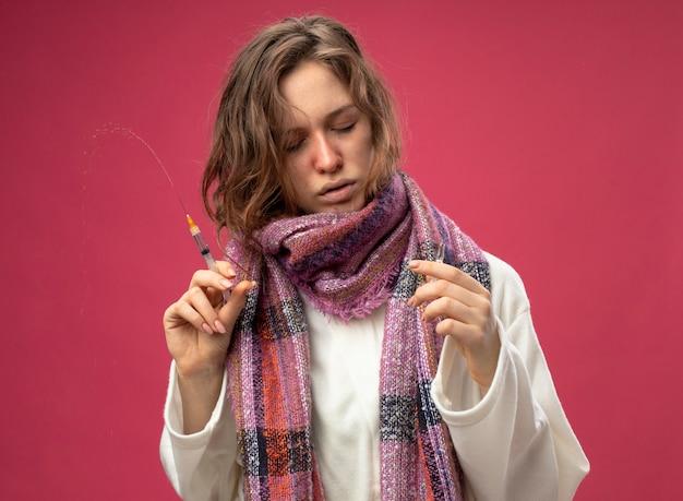 Молодая больная девушка с закрытыми глазами в белом халате и шарфе держит шприц и смотрит на ампулу в руке, изолированной на розовой стене