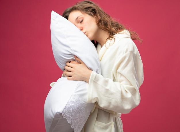 Молодая больная девушка с закрытыми глазами в белом халате обняла подушку, изолированную на розовом