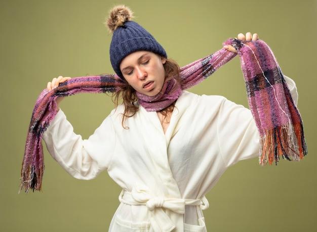 Giovane ragazza malata con gli occhi chiusi che indossa una veste bianca e cappello invernale con sciarpa che mostra gesto di suicidio con sciarpa isolato su verde oliva