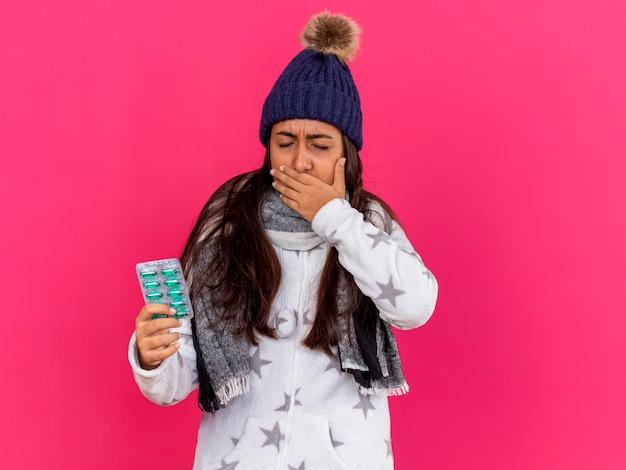 Молодая больная девушка с закрытыми глазами в зимней шапке с шарфом держит таблетки, покрытые рукой, болит рот, изолированный на розовом