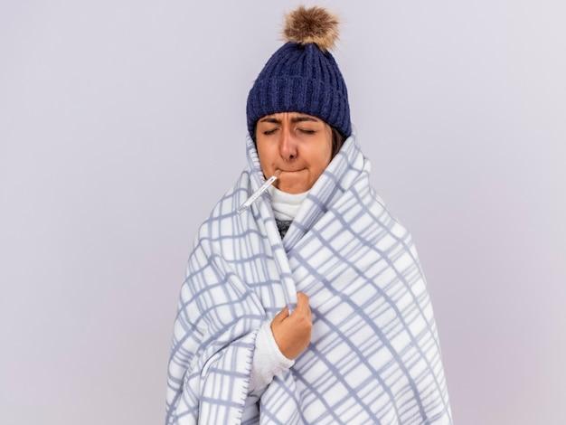 Giovane ragazza malata con gli occhi chiusi che indossa un cappello invernale con sciarpa avvolta in un plaid mettendo il termometro in bocca