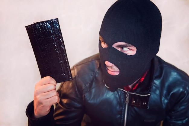 Молодой злонамеренный мужчина в черной маске держит черный кожаный женский кошелек и смотрит на свою добычу. грабитель украл бумажник. половина кадра вора в балаклаве с кошельком. дело карманников.