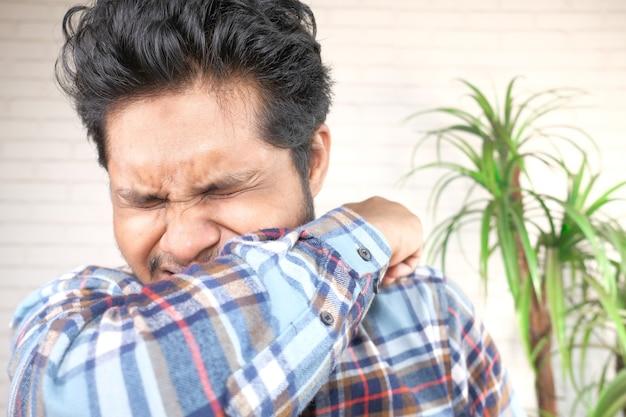 그녀의 코와 입을 팔로 덮고있는 젊은 아픈 남자.