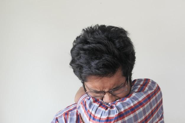 若い病気の男が彼女の鼻と口を腕で覆っています。