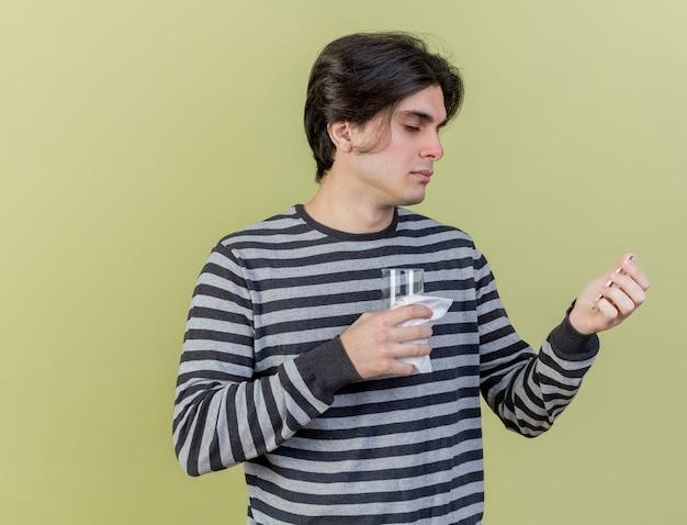 Giovane uomo malato azienda pillole con bicchiere d'acqua isolato su pensativo verde oliva