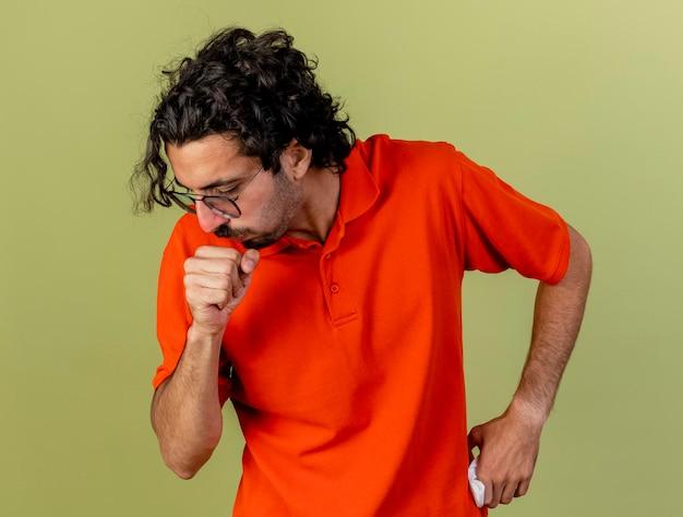 입 근처에 허리와 주먹에 손을 유지하고 올리브 녹색 벽에 고립 된 기침 안경을 착용하는 젊은 아픈 남자