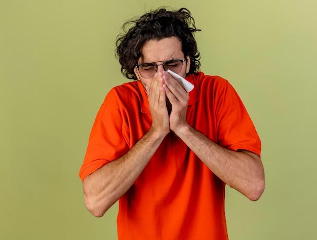 Молодой больной человек в очках держит салфетку, держа руки во рту и чихая, изолирован на оливково-зеленой стене с копией пространства