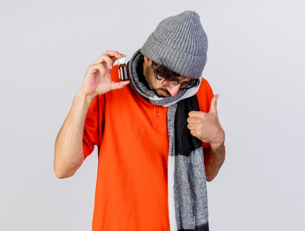ガラスの冬の帽子とスカーフを身に着けている若い病気の人は、白い壁に隔離された頭を下に傾けて親指を示すガラスの薬を示しています