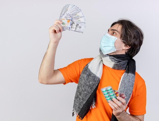 スカーフと医療マスクを身に着けている若い病気の人は、錠剤を保持し、白い背景で隔離の現金を上げて見ています