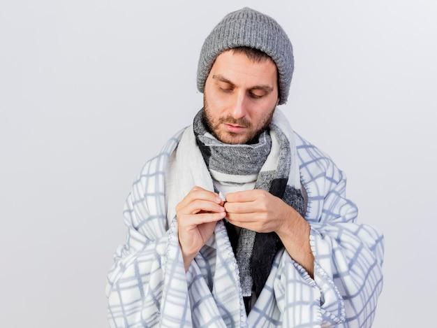 격자 무늬 오프닝 석고에 싸여 겨울 모자와 스카프를 착용하는 젊은 아픈 남자는 흰색에 고립