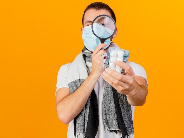 Giovane uomo malato che indossa cappello invernale e mascherina medica tenendo e guardando le pillole con lente di ingrandimento isolato su giallo