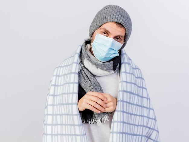 Giovane uomo malato che indossa cappello invernale e sciarpa con mascherina medica avvolta in un plaid che tengono le mani insieme