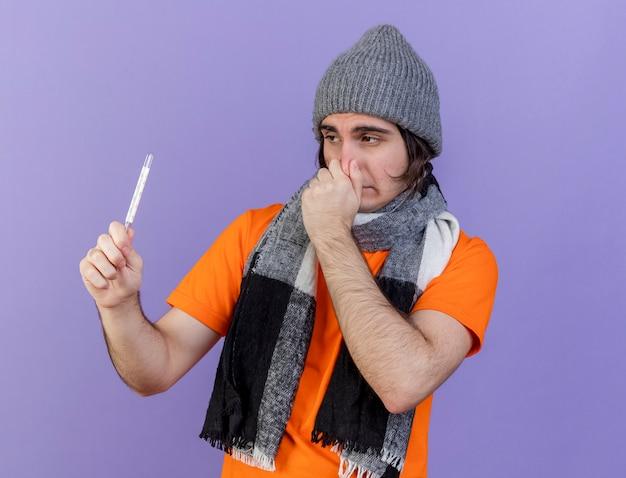 Молодой больной человек в зимней шапке с шарфом, держащий и смотрящий на градусник схватился за нос, изолированный на фиолетовом