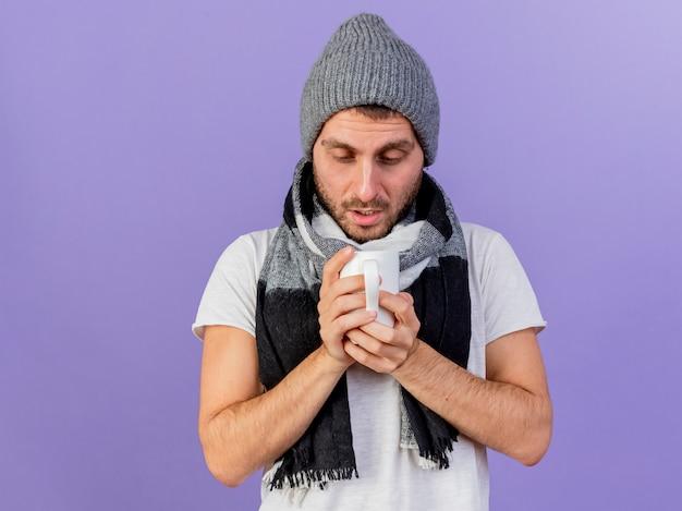 Giovane uomo malato che indossa il cappello invernale con sciarpa che tiene e guardando la tazza di tè isolato su sfondo viola