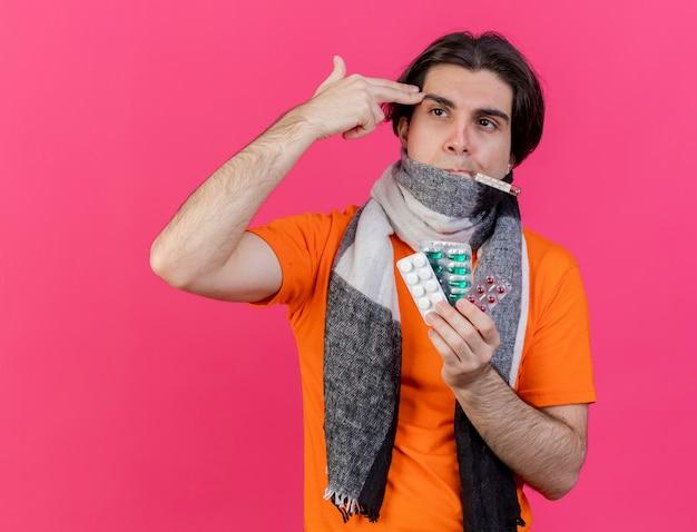 ピンクに分離されたピストルのジェスチャーで自殺を示す温度計を口に入れて丸薬を保持しているスカーフと冬の帽子をかぶっている若い病気の男