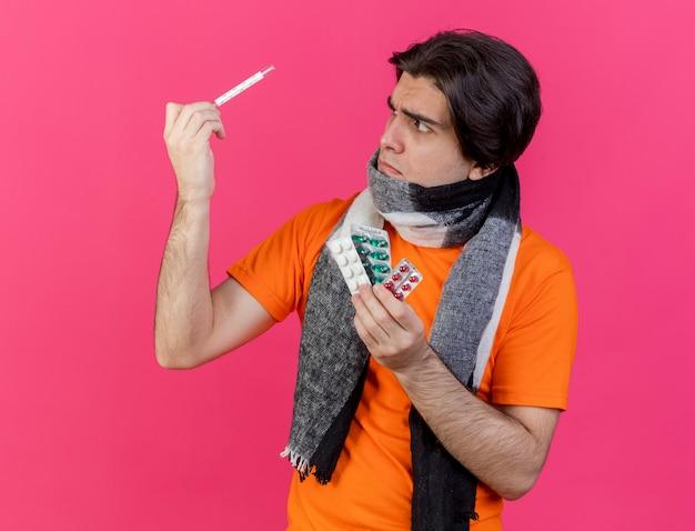 Giovane uomo malato che indossa un cappello invernale con sciarpa tenendo le pillole alzando e guardando il termometro isolato sul rosa