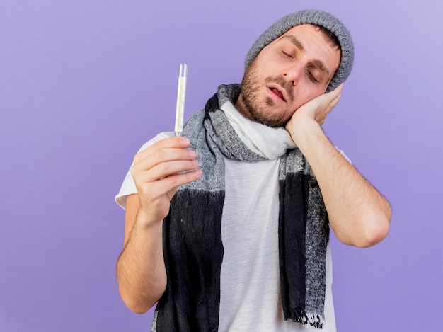 Молодой больной человек в зимней шапке с шарфом держит термометр и кладет руку на щеку, изолированную от фиолетового