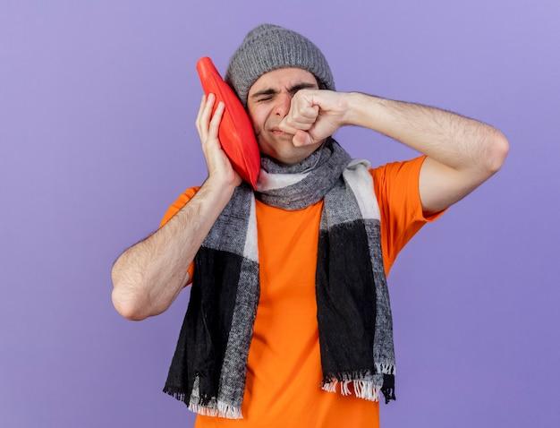 Giovane uomo malato che indossa un cappello invernale con sciarpa mettendo la borsa dell'acqua calda sulla guancia asciugandosi il viso con la mano isolato su viola