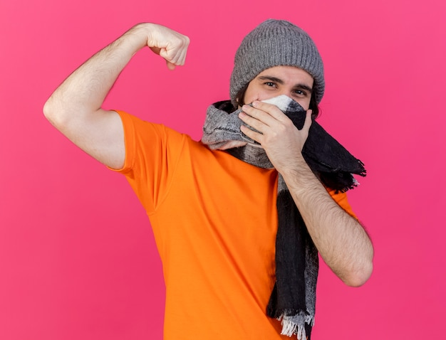 강한 제스처를 보여주는 스카프와 겨울 모자를 쓰고 아픈 젊은이 핑크에 고립 된 스카프로 얼굴을 덮었습니다.