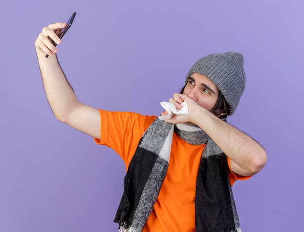 スカーフと冬の帽子をかぶっている若い病気の男は、紫色の背景で隔離の手でselfieと鼻を拭きます