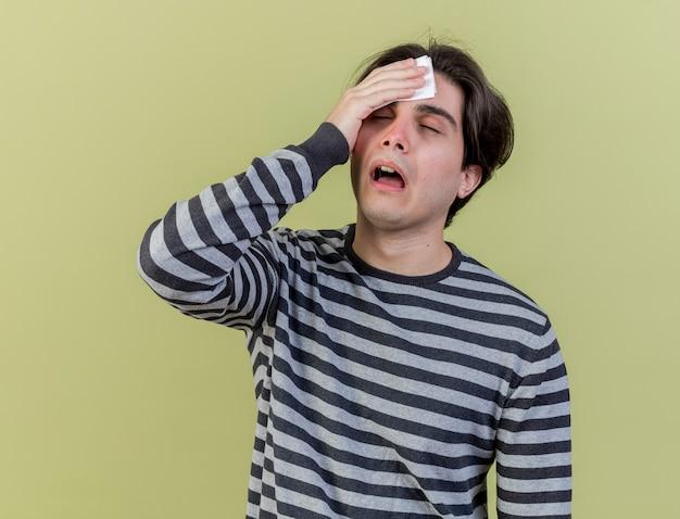オリーブグリーンで隔離のナプキンで額を拭く若い病気の男