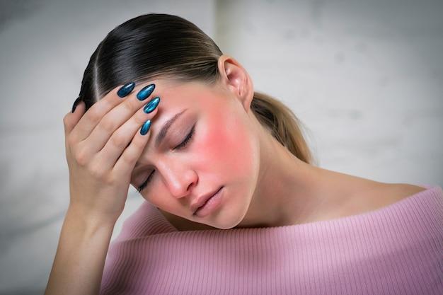 젊은 아픈 여자는 더위, 고온, 두통 및 편두통으로 고통 받고 있습니다