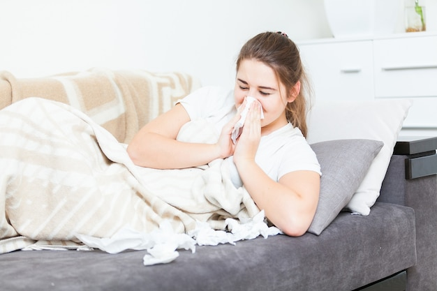 Young ill woman lying in bed and sneezing in paper tissue