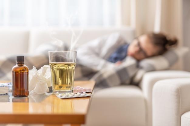젊은 아픈 여자는 꿀과 레몬으로 뜨거운 차를 마시는 계절 illnes와 함께 침대에 담요 아래에 누워. 그녀는 질병을 밀어내기 위해 약과 기침 시럽을 먹습니다.