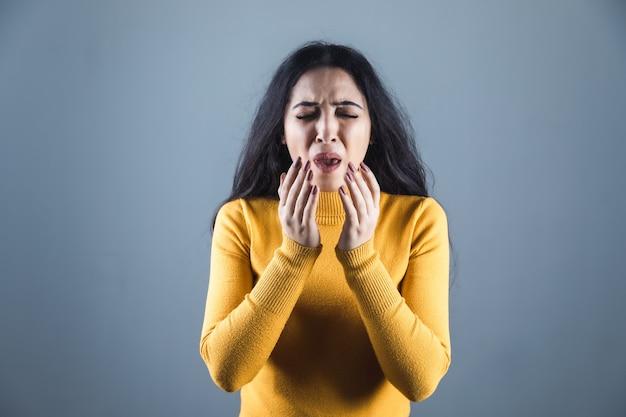 Молодая больная женщина на сером фоне
