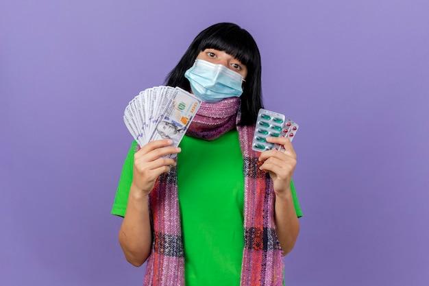 마스크와 스카프를 착용하는 젊은 아픈 여자 복사 공간이 보라색 벽에 고립 된 전면을보고 돈과 캡슐 팩을 들고