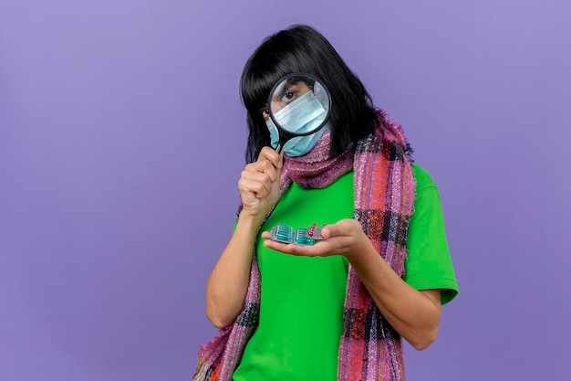 コピースペースと紫色の壁に分離された拡大鏡を通して正面を見てカプセルのパックを保持しているマスクとスカーフを身に着けている若い病気の女性