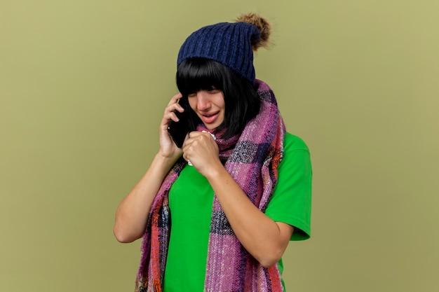 Giovane donna malata che indossa cappello invernale e sciarpa parlando al telefono guardando dritto tenendo il tovagliolo tosse isolato sulla parete verde oliva con lo spazio della copia